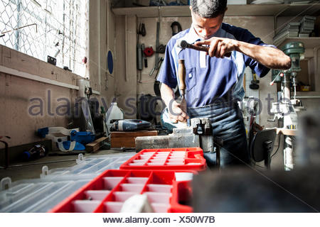 Young man using hammer and chisel in repair workshop - Stock Photo