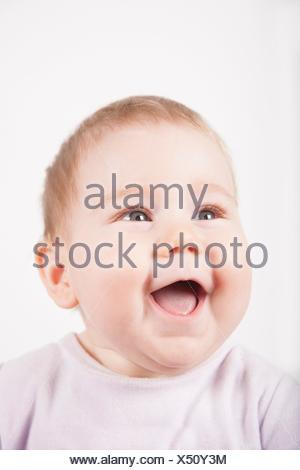 portrait of eight months age blonde lovely cute baby pink velvet onesie smiling happy face isolated on white. - Stock Photo