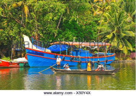 canoe and moored fishing boats in backwaters between Kollam and Cochin, Kerala, India - Stock Photo