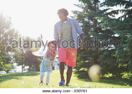 Portrait of cute girl holding fathers hand at park - Stock Photo