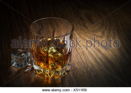 Whiskey with ice in glass on the wood - Stock Photo
