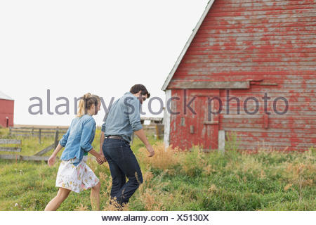 Young couple walking towards barn on rural property. - Stock Photo