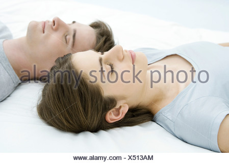 Couple sleeping, heads side by side - Stock Photo
