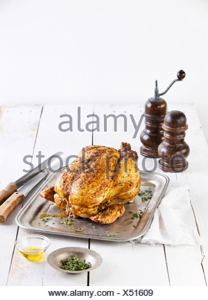 Whole roasted chicken on white wooden background - Stock Photo