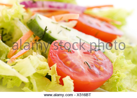 Fresh garden salad with tomato, cucumber and lettuce as closeup - Stock Photo