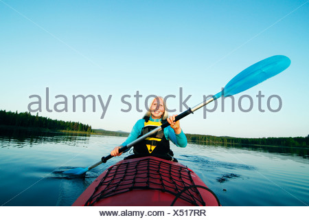 Smiling woman holding paddle - Stock Photo