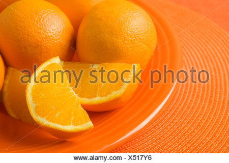 Closeup of oranges and orange slices on plate - Stock Photo