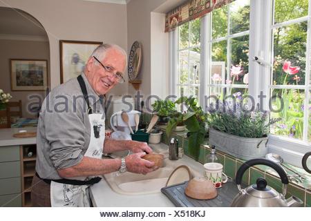 Senior man in kitchen, washing dishes - Stock Photo