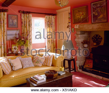 Yellow sofa with floral cushions in cheerful red country sitting room with inglenook fireplace and floral curtains - Stock Photo