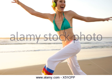 Young female wearing a headset jumps and smiles at the beach. - Stock Photo