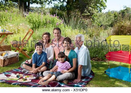 Three generation family in park having picnic - Stock Photo