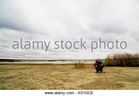 Young man hiking, crouching, taking photograph of lake view, rear view - Stock Photo