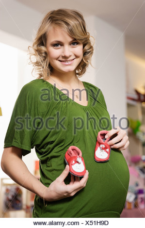 Pregnant woman buying baby shoes - Stock Photo