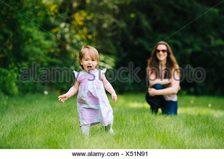 Female toddler running away from watching mother in park - Stock Photo