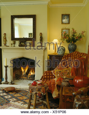 ... Patterned Red Throw And Cushions On Armchair Beside Lighted Fire In  Fireplace With Lighted Lamp On
