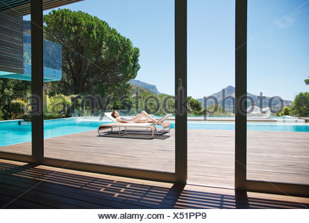 Woman sunbathing on lounge chair next to luxury swimming pool with mountain view - Stock Photo