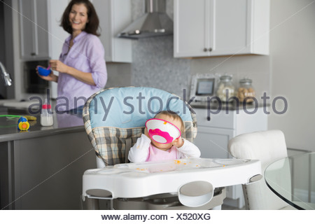 Baby sitting in high chair at home eating - Stock Photo