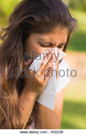 Woman blowing nose with tissue paper - Stock Photo