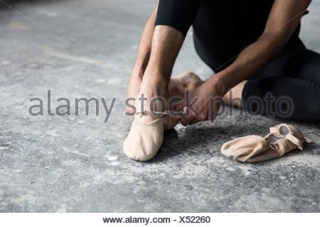 Dancer wearing ballet shoe in studio - Stock Photo