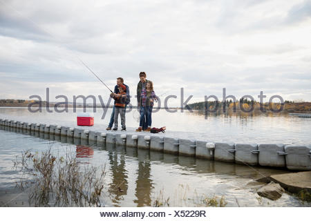 Family fishing on lake jetty - Stock Photo