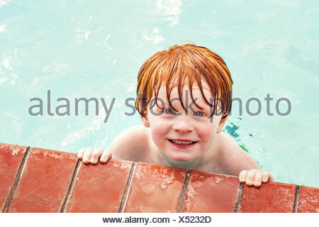Portrait of smiling boy in a swimming pool - Stock Photo