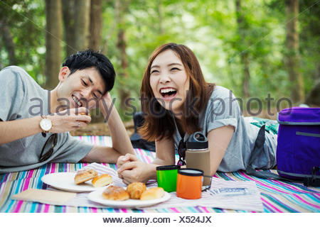 Young woman and man having a picnic in a forest. - Stock Photo