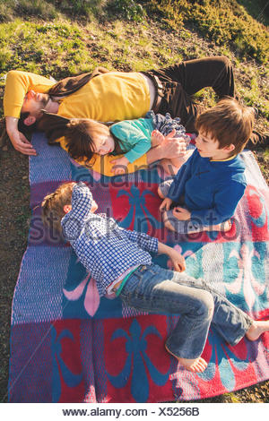Father and three children lying on picnic blanket - Stock Photo
