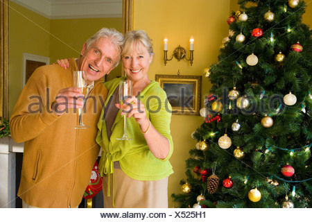 Senior couple with champagne flutes by Christmas tree, portrait - Stock Photo