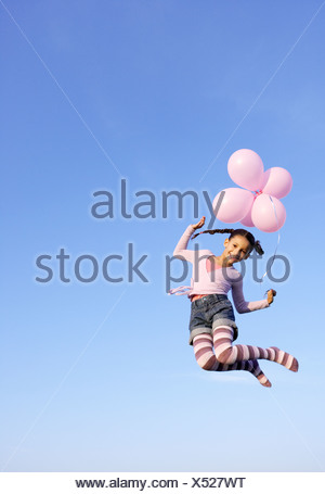 Girl jumping in the air with balloons - Stock Photo