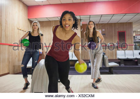 A young woman bowling with friends. - Stock Photo