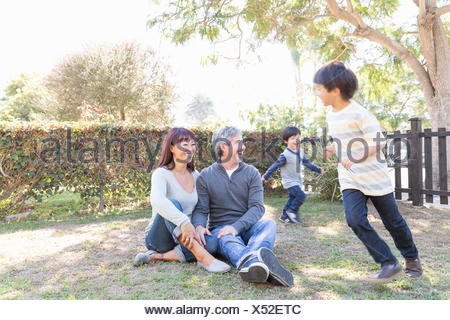 Happy young family sitting and playing in grass - Stock Photo