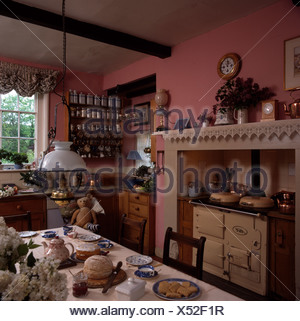 Cream Aga in pink kitchen with table set for tea below Victorian style brass lantern - Stock Photo