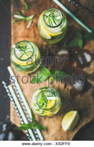 Citrus fruit and herbs infused sassi water for detox, healthy eating, dieting in glass bottles on wooden board over dark background, top view, selecti - Stock Photo