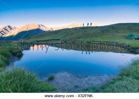 Silhouettes of hikers are reflected in the lake with Mont De La Saxe on the background Courmayeur Aosta Valley Italy Europe - Stock Photo