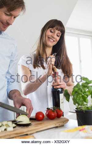 Mid adult woman opening wine bottle while mature man cutting vegetable, smiling - Stock Photo