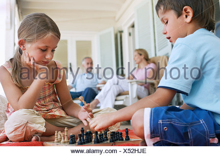 Brother and sister (7-9) playing chess on porch, parents in background - Stock Photo
