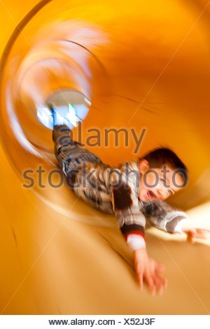 a little boy slides down a tubular slide. Motion Blur. - Stock Photo