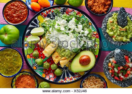 Green enchiladas Mexican food with guacamole and sauces on colorful table. - Stock Photo