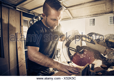 Male carpenter sawing plank of wood in workshop - Stock Photo