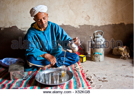 Elderly Berber man wearing a turban sitting on the floor on a rug pouring traditional mint tea from a silver jug, Kelaa M'gouna - Stock Photo