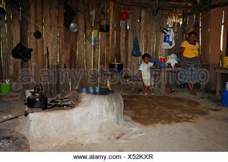 One-room flat, Mayan woman, small boy, fireplace, kitchen utensils, water boiler, Punta Gorda, Belize, Central America - Stock Photo