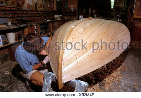 A traditional Beetlecat builder working on the bottom of a new boat at the International Yacht Restoration School in Newport, Rh - Stock Photo