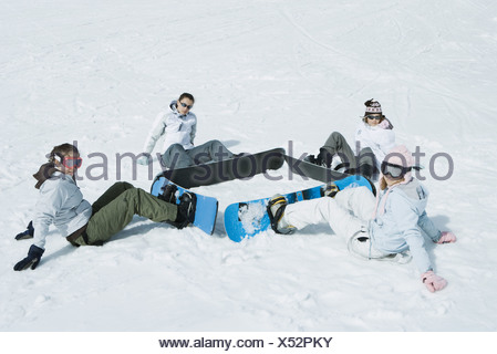 Four young snowboarders sitting on the ground in a square, looking at camera - Stock Photo