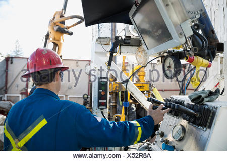 Male engineer operating drilling rig at control panel - Stock Photo