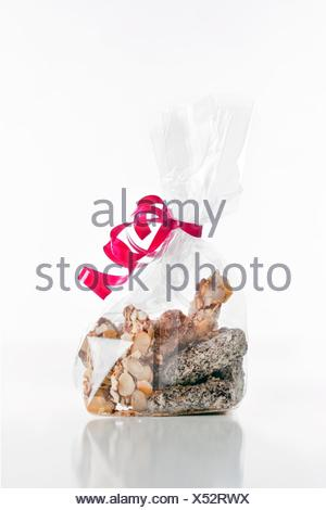assortment of delicious chocolate truffles in bag with red ribbon - Stock Photo