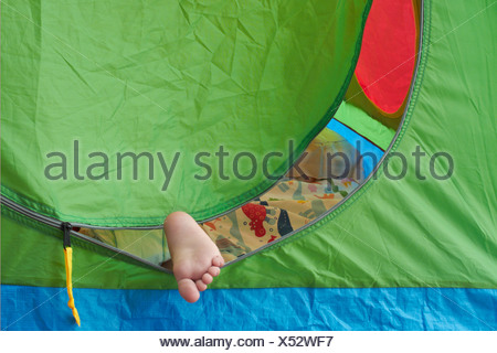 Toddler's foot sticking out of tent - Stock Photo