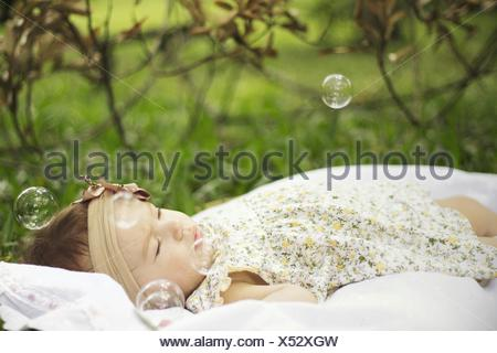 Baby Girl Surrounded By Bubbles In Park - Stock Photo