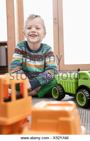Portrait of smiling little boy sitting on ground of his kindergarten - Stock Photo