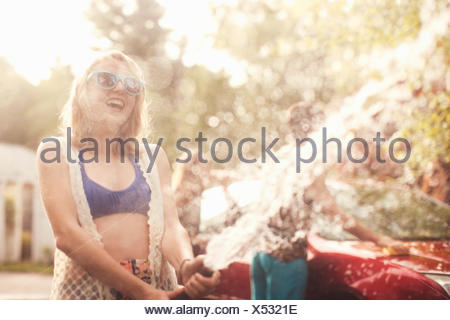 Young woman spraying water from hosepipe - Stock Photo