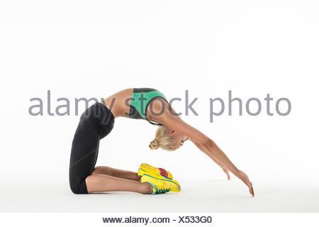 Rhythmic gymnast doing exercise in studio. - Stock Photo